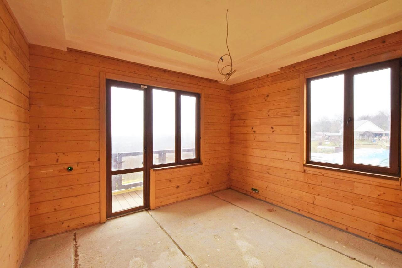 В комнате много окон с балконом