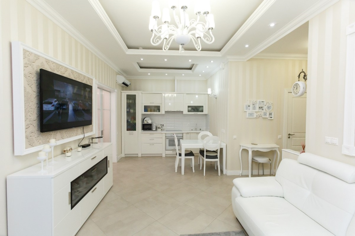 Кухня гостиная с TV зоной и белым диваном
